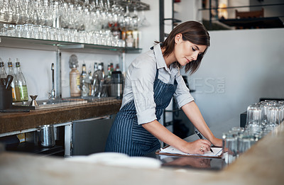 Buy stock photo Cropped shot of an attractive young woman working behind the bar in her coffee shop