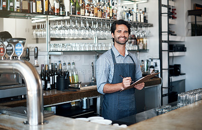 Buy stock photo Cropped portrait of a handsome young man using a clipboard while working in his coffee shop