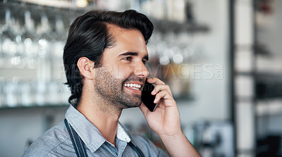 Buy stock photo Cropped shot of a handsome young man using a cellphone while working in his coffee shop