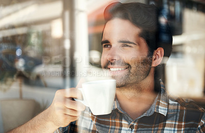 Buy stock photo Cropped shot of a handsome young man enjoying a cup of coffee while sitting in a coffee shop