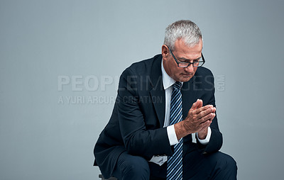 Buy stock photo Studio shot of a mature businessman praying against a grey background