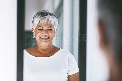 Buy stock photo Shot of a cheerful mature woman looking at her reflection in a mirror at home