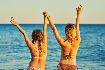 Buy stock photo Rearview shot of unrecognizable women at the beach