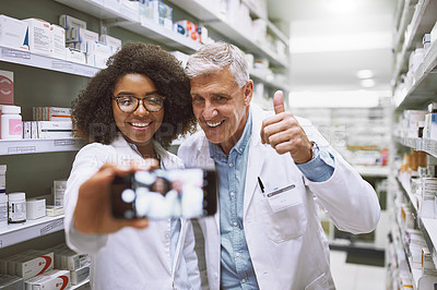 Buy stock photo Shot of two cheerful pharmacists posing together for a self portrait while one shows thumbs up