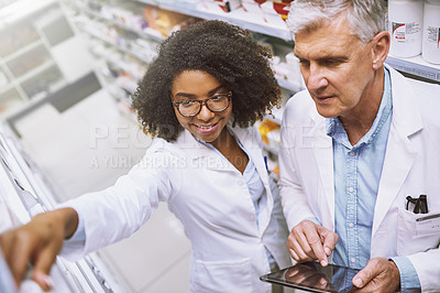Buy stock photo High angle shot of two focused pharmacist walking around and doing stock inside of a pharmacy