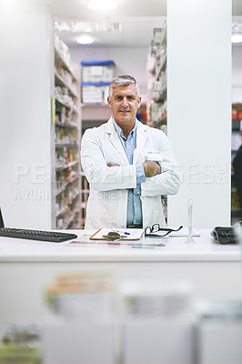 Buy stock photo Portrait of a cheerful mature male pharmacist standing with arms folded while looking at the camera in a pharmacy