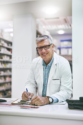 Buy stock photo Portrait of a confident mature male pharmacist making notes in a book on the counter while looking at the camera