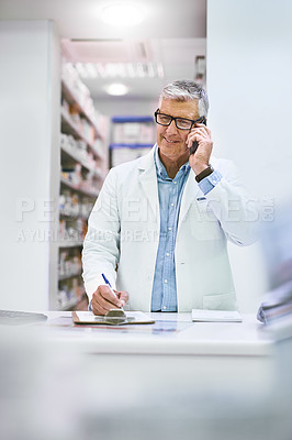Buy stock photo Shot of a cheerful mature male pharmacist making notes while being on the phone in the pharmacy