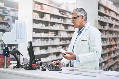 Buy stock photo Shot of a focused mature male pharmacist typing on a computer keyboard while holding a medication box