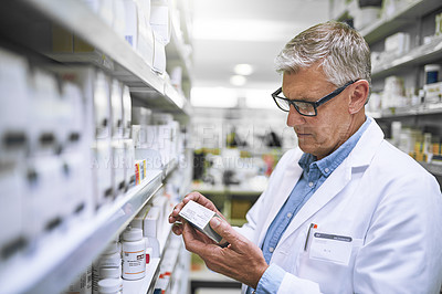 Buy stock photo Shot of a focused mature male pharmacist holding a medication box and reading it in a pharmacy