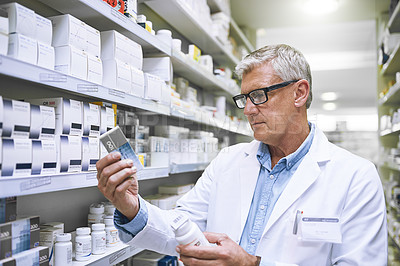 Buy stock photo Shot of a focused mature male pharmacist holding two medication boxes and reading it in a pharmacy
