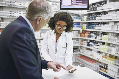 Buy stock photo Shot of a cheerful young female pharmacist giving a customer prescription meds over the counter in a pharmacy