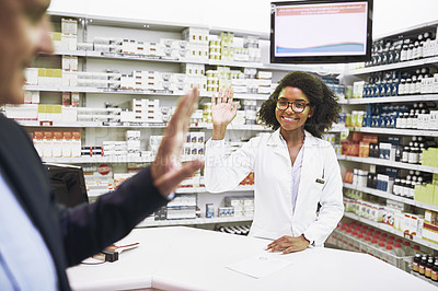 Buy stock photo Shot of a cheerful young female pharmacist greeting a customer inside of the pharmacy