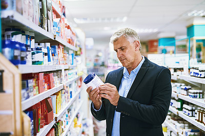 Buy stock photo Shot of a well dressed mature man browsing a pharmacy's shelves looking for the right medication to buy
