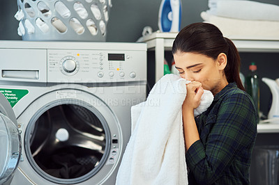 Buy stock photo Cropped shot of an attractive young woman smelling a freshly washed towel while doing laundry at home