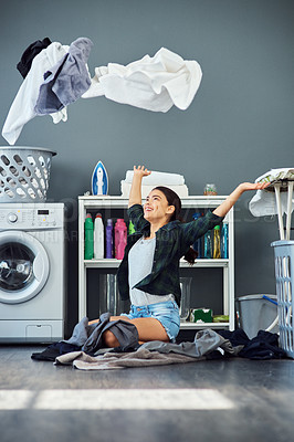 Buy stock photo Full length shot of an attractive young woman throwing her washing in the air while doing laundry at home