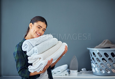 Buy stock photo Cropped portrait of an attractive young woman carrying a pile of towels while doing laundry at home