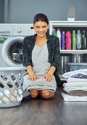 Buy stock photo Full length portrait of an attractive young woman folding a towel while doing laundry at home