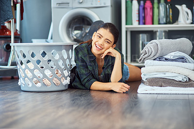 Buy stock photo Portrait of an attractive young woman lying on the floor while doing laundry at home