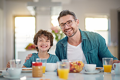 Buy stock photo Cropped portrait of a handsome man having breakfast with his son at their dining room table