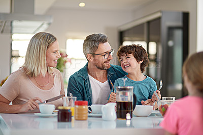 Buy stock photo Cropped shot of a happy family of four having breakfast while sitting at their dining room table