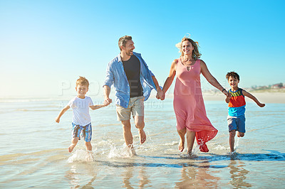 Buy stock photo Shot of a happy family enjoying some quality time together at the beach
