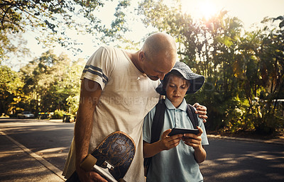 Buy stock photo Shot of a father and son walking outside