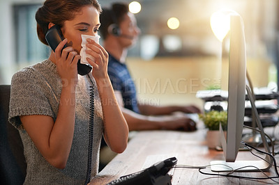 Buy stock photo Shot of a young businesswoman blowing her nose while talking on a phone in an office