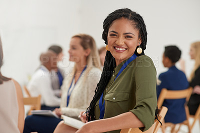 Buy stock photo Portrait of a cheerful young businesswoman sitting down in a boardroom with colleagues during a presentation
