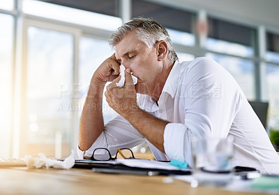 Buy stock photo Shot of a mature businessman blowing his nose in the office
