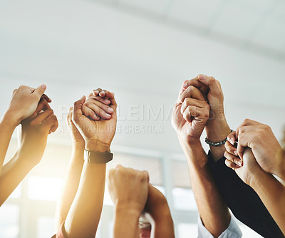 Buy stock photo Closeup shot of a group of unrecognizable businesspeople holding hands while raising their arms