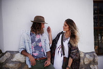 Buy stock photo Shot of a trendy young couple standing together against the wall of a building outside