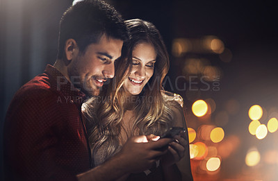 Buy stock photo Shot of a young couple using their smartphones together at night