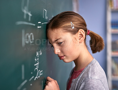 Buy stock photo Cropped shot of an elementary school girl pressing her head against the blackboard with frustration in class
