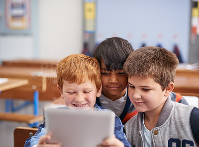 Buy stock photo Cropped shot of elementary school children using a tablet in class