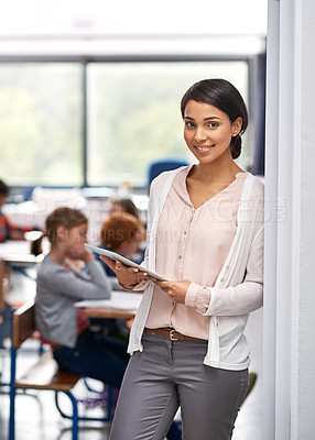Buy stock photo Portrait of a happy young teacher holding a tablet with her students in the background
