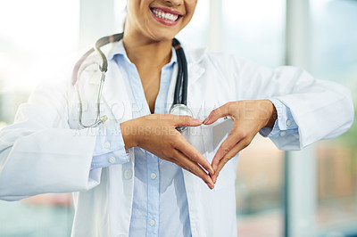 Buy stock photo Portrait of a young female doctor making a heart shape with her hands