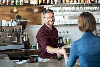 Buy stock photo Cropped shot of a handsome male barista taking payment from a female customer