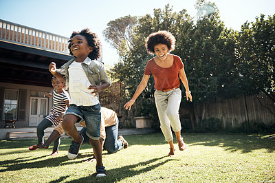Buy stock photo Shot of a cheerful little boy and girl being chased by their parents outside in a garden during the day