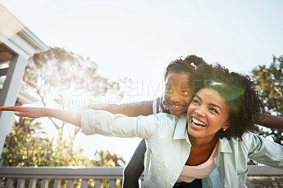 Buy stock photo Shot of a cheerful young mother giving her little daughter a piggyback ride outside during the day