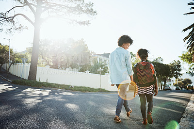 Buy stock photo Rearview shot of a cheerful young mother and her daughter walking down the street together outside during the day