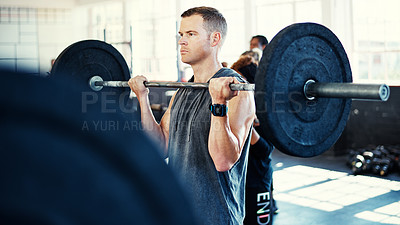 Buy stock photo Shot of a man working out with a barbell in his session at the gym