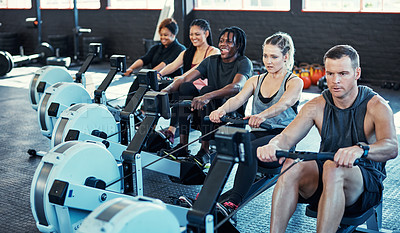Buy stock photo Shot of a fitness group working out on rowing machines in their session at the gym