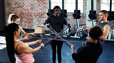 Buy stock photo Shot of a fitness group working out with resistance bands in their session at the gym