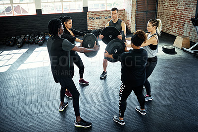 Buy stock photo Shot of a fitness group using weight plates in their session at the gym