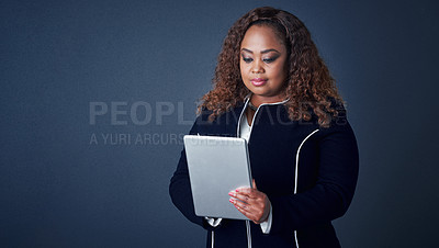 Buy stock photo Studio shot of a confident young businesswoman working on her digital tablet while standing against a blue background
