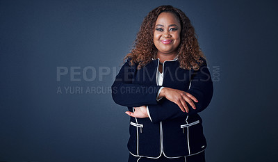 Buy stock photo Portrait of a cheerful young businesswoman standing with her arms folded while standing against a blue background