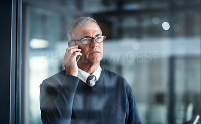 Buy stock photo Shot of a mature businessman talking on a cellphone while working late in an office