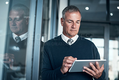 Buy stock photo Shot of a mature businessman using a digital tablet while working late in an office