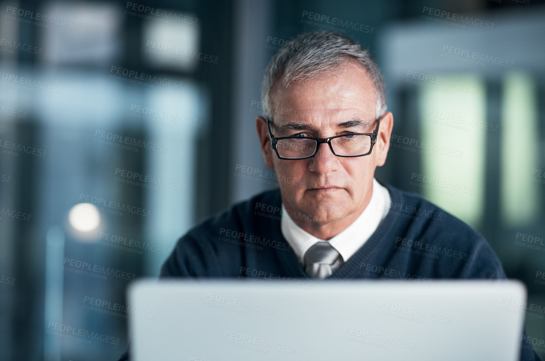 Buy stock photo Shot of a mature businessman working late on a laptop in an office